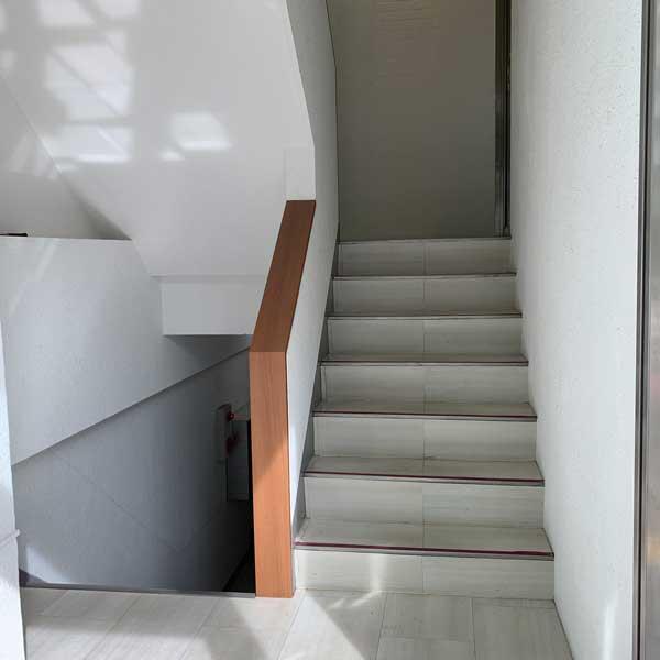 建物に入りましたら、この階段を登った壁裏側にあるエレベーターにお乗りください。